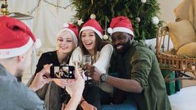 Un grupo de personas de diversas razas que plantean y que toman imágenes en el teléfono Los amigos alegres en los sombreros de Pa almacen de metraje de vídeo