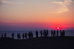 Un grupo de personas en el fondo de la puesta del sol stock de ilustración