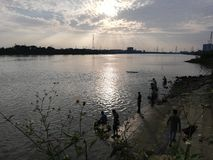 Un grupo de personas pescaba por el río en la puesta del sol imagenes de archivo