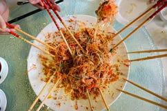 Un grupo de personas que mezcla y que lanza el plato de Yee Sang con tajada se pega Fotografía de archivo