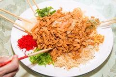 Un grupo de personas que mezcla y que lanza el plato de Yee Sang con tajada se pega Yee Sang es una delicadeza popular tomada dur Fotografía de archivo libre de regalías