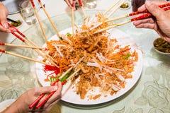 Un grupo de personas que mezcla y que lanza el plato de Yee Sang con tajada se pega Yee Sang es una delicadeza popular tomada dur Foto de archivo