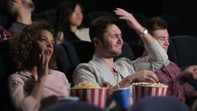 Un grupo de personas que mira una película el mostrar de la emoción metrajes