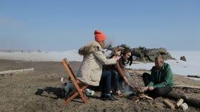 Un grupo de personas que se sienta alrededor de la hoguera backpacking almacen de metraje de vídeo
