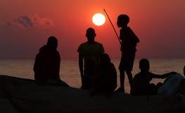 Un grupo de pescadores y de niños en la salida del sol, el lago Malawi Imágenes de archivo libres de regalías