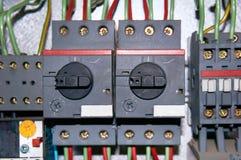 Un grupo de retransmisiones eléctricas con los alambres conectados fotos de archivo
