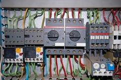 Un grupo de retransmisiones eléctricas con los alambres conectados foto de archivo