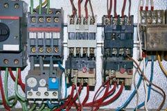 Un grupo de retransmisiones eléctricas con los alambres conectados imagenes de archivo