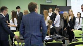 Un grupo de reunión del primer año del estudiante en la universidad Estudiantes femeninos y masculinos que vienen a la sala de cl almacen de metraje de vídeo