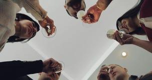 Un grupo de socios comerciales que tintinean los vidrios con champán en la oficina almacen de metraje de vídeo