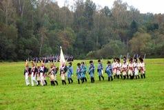 Un grupo de soldados-reenactors marcha con una bandera Fotos de archivo libres de regalías