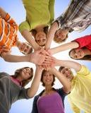 Un grupo de teenages jovenes que llevan a cabo las manos juntas Imagen de archivo libre de regalías