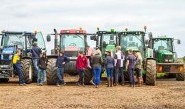 Un grupo de tractores parqueó para arriba con los granjeros jovenes Imagen de archivo libre de regalías