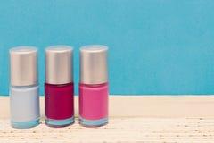 Un grupo de tres botellas coloridas del esmalte de uñas del adolescente Imagenes de archivo
