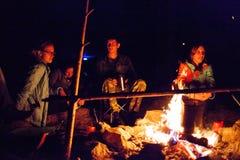 Un grupo de turistas que se sientan alrededor de la hoguera en la noche Imágenes de archivo libres de regalías