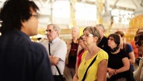 Un grupo de turistas recolecta alrededor de un guía turístico metrajes
