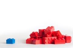 Un grupo grande de bloques rojos del lego y de un azul Fotos de archivo