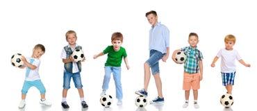 Un grupo grande de muchachos con los balones de fútbol Foto de archivo libre de regalías
