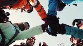 Un grupo unido de escaladores se une a junto, cruza sus manos antes de ir almacen de metraje de vídeo