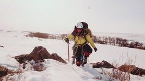 Un grupo valiente de escaladores sube la superación del tiempo severo del invierno y de la nieve encima de una colina grande y es metrajes