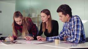 Un gruppo creativo di affari di tre genti che si incontrano in un ufficio moderno e che discutono le idee di affari mentre sedend archivi video
