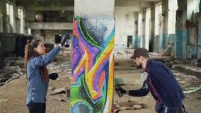 Un gruppo creativo di due pittori urbani sta disegnando i graffiti con la pittura di spruzzo mentre decorava il vecchio magazzino archivi video