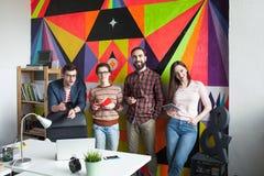 Un gruppo creativo di quattro colleghi che lavorano nell'ufficio moderno Immagine Stock
