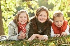 Un gruppo di 3 bambini che si distendono all'aperto in autunno Immagini Stock Libere da Diritti