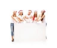 Un gruppo di adolescenti felici ed emozionali in cappelli di Natale Fotografia Stock Libera da Diritti