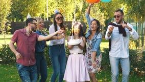 Un gruppo di amici in cappello del partito e corno del partito divertendosi e celebrando il compleanno video d archivio