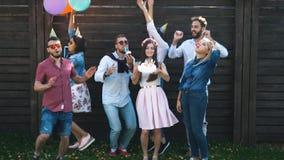 Un gruppo di amici in cappello del partito e corno del partito divertendosi e celebrando il compleanno stock footage