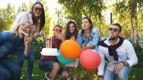 Un gruppo di amici in cappello del partito e corno del partito divertendosi e celebrando il compleanno archivi video