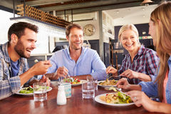 Un gruppo di amici che mangiano ad un ristorante Immagini Stock Libere da Diritti