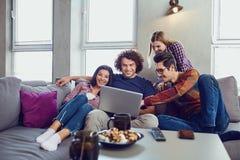 Un gruppo di amici degli studenti nello svago con un computer portatile insieme immagini stock libere da diritti