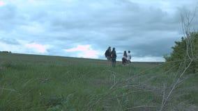 Un gruppo di amici in mezzo al campo contro un fondo delle nuvole spesse Gli amici stanno camminando in natura intorno archivi video