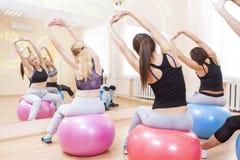 Un gruppo di cinque atleti femminili caucasici che hanno allungamento degli esercizi Immagine Stock