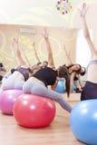Un gruppo di cinque atleti femminili caucasici che hanno allungamento degli esercizi con Fitballs Fotografie Stock Libere da Diritti