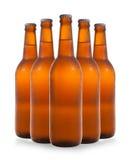 Un gruppo di cinque bottiglie di birra in una formazione di diamante sul BAC bianco Fotografia Stock