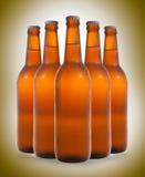 Un gruppo di cinque bottiglie di birra in una formazione di diamante sul BAC di colore Immagini Stock