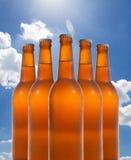 Un gruppo di cinque bottiglie di birra in una formazione di diamante sul backg del cielo Immagine Stock