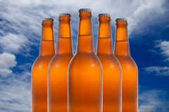 Un gruppo di cinque bottiglie di birra in una formazione di diamante sul backg del cielo Fotografia Stock