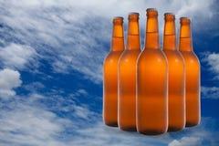 Un gruppo di cinque bottiglie di birra in una formazione di diamante sul backg del cielo Fotografie Stock