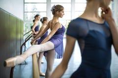 Un gruppo di cinque giovani ballerini si è preparato in una classe di ballo vicino alle sedere Immagini Stock