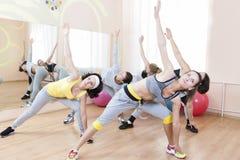 Un gruppo di cinque giovani femmine caucasiche che fanno allungamento degli esercizi nella sede di sport Immagine Stock