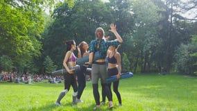 Un gruppo di cinque misura le donne felici che danno su cinque in parco dopo l'allenamento, celebrante il successo Definendo gli  stock footage