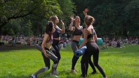 Un gruppo di cinque misura le donne felici che danno su cinque in parco dopo l'allenamento, celebrante il successo Definendo gli  video d archivio