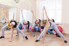 Un gruppo di cinque sportive professionali che fanno allungamento degli esercizi con il tronco che piega nella classe di sport Immagine Stock Libera da Diritti