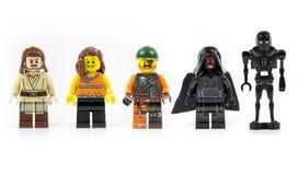 Un gruppo di cinque vari mini caratteri di Lego isolati su bianco fotografia stock
