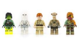 Un gruppo di cinque vari mini caratteri di Lego isolati su bianco immagine stock