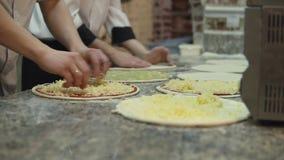 Un gruppo di cuochi sotto forma di formaggio uniformemente messo sui cerchi della pasta della pizza stock footage